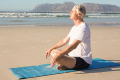 Side view of senior man meditating on mat at beach Stock Photo