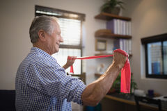 Side view of senior man pulling resistance band in hospital ward Royalty Free Stock Images