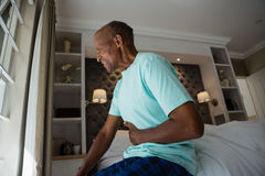 Side view of senior man suffering from stomachache at home Stock Photos