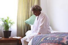 Senior woman sitting upset in nursing home. Side view of senior mixed race woman sitting upset in nursing home royalty free stock photo