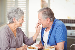 Side view of senior woman feeding husband while sitting at table Royalty Free Stock Photography