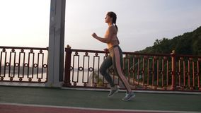 Side view of senior woman jogging across bridge