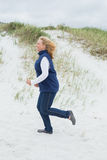 Side view of a senior woman jogging at beach Royalty Free Stock Photos