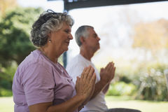Side view of senior woman meditating with man Royalty Free Stock Photos