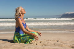 Side view of senior woman meditating while sitting on shore stock photos