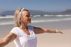 Side view of senior woman standing with arms outstretched at beach stock image