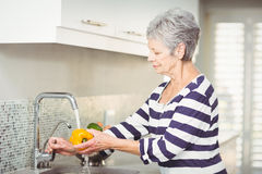 Side view of senior woman washing bell pepper Stock Photo