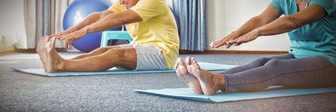 Side view of seniors doing exercises. In studio stock images
