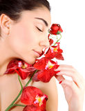 Arabic woman with red orchid. Side view of sensual arabic woman with closed eyes isolated on white background, fresh red orchid flowers, luxury spa salon, joy Stock Photo