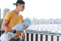 Serious teenager keeping skate in hands royalty free stock images