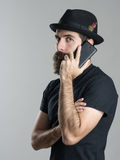 Side view of serious bearded hipster talking on the mobile phone looking at camera Royalty Free Stock Photography