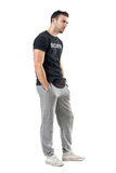 Side view of serious doubtful bouncer in sportswear looking at distance. Full body length portrait isolated on white studio background Stock Images