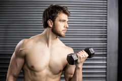 Side view of serious man lifting weight Stock Photo