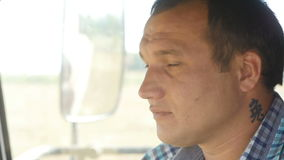 Side view serious man sits and turns head in combine cabine stock footage