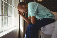 Side view of serious senior man sitting on bed by window. At home Stock Images