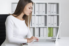 Side view of a serious woman typing Stock Images
