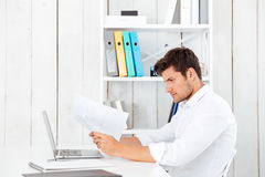 Side view of a serious young businessman working with documents Stock Photo