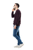Side view of serious young casual man talking on the phone looking away. Full body length portrait isolated over white studio background Stock Photo