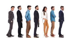 Side view of seven different people standing in line. E view of seven people with different reactions standing in line on white background, full body picture stock photos