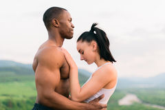 Side view of sexy fit mixed race couple with perfect bodies in sportswear softly embracing on mountains landscape Stock Photo