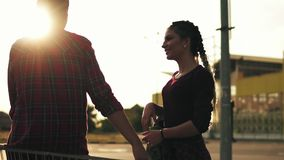 Side view of a girl with long braids holding a skateboard and talking to her girlfriend that is sitting on the. Shopping cart in the parking near a shopping stock video footage