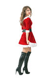 Side view of sexy Santa girl walking away turning head and smiling to camera. Full body length portrait isolated over white studio background Stock Images