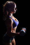 Side view of sexy woman lifting dumbbell Stock Photo
