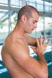 Side view of shirtless fit swimmer by pool at leisure center Royalty Free Stock Photos