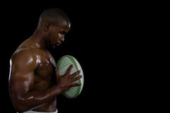 Side view of shirtless male athlete holding rugby ball Royalty Free Stock Images