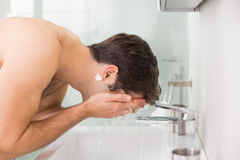 Side view of shirtless man washing face in bathroom Royalty Free Stock Images
