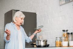 Side view of shocked senior lady checking saucepan on stove. In kitchen stock photography