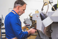 Side view of shoe grinding. Man repairing heel of a shoe on an industrial grinder machine Royalty Free Stock Photo