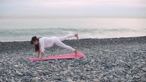 Woman doing core workout on a beach. Side view shooting of a core body workout on a beach shore in the morning, one-legged plank on yoga mat. Yoga practice by stock footage