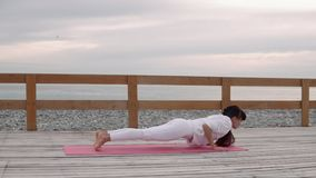 Flexible woman does yoga on fresh air by sea. stock video footage