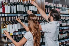 side view of shop assistants arranging bottles of wine royalty free stock images