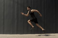 A side view shot of a fit young, athletic man jumping and runnin. G doing cardio interval training against a grey background. Fitness male exercising, outdoors royalty free stock photos