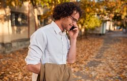 Side view shot of handsome businessman posing on the autumn street while walking outdoors and using smartphone for calling. stock photos