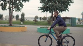 Man on a bike ride. Side view shot of a man with a beard on a bicycle ride in city, free ride on empty streets. Outdoor activities stock footage