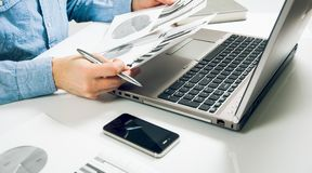 Side view shot of a man`s hands using smart phone in interior, rear view of business man hands busy using cell phone at office de. Sk, young male student typing Royalty Free Stock Photo