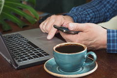 Side view shot of a man`s hands using smart phone and laptop sitting at wooden table. Close up. Stock Photography