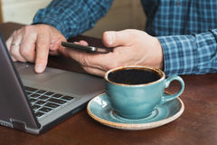 Side view shot of a man`s hands using smart phone and laptop sitting at wooden table with cup of black coffee. Close up. royalty free stock photo