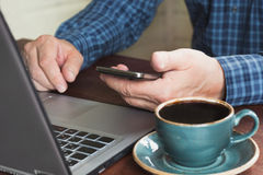 Side view shot of a man`s hands using smart phone and laptop sitting at wooden table with cup of coffee. Close up. Stock Image