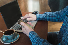 Side view shot of a man`s hands using smart phone and laptop sitting at wooden table with cup of coffee. Close up. Royalty Free Stock Photography