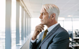 Thoughtful senior businessman standing by window. Side view shot of senior businessman standing by window and looking outside. Caucasian male executive thinking Stock Photography