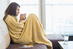 Side view of sick woman having coffee on sofa in living room. Side view of sick women having coffee on sofa in living room royalty free stock photos