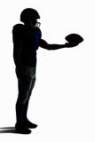 Side view of silhouette American football player holding ball Stock Images