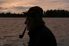 Side view silhouette of an old fisherman smoking a pipe. Side view silhouette portrait of an old fisherman, standing by the ocean smoking a pipe in the pink Royalty Free Stock Image