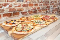 Side view of six different pizzas on a wooden board stock photo