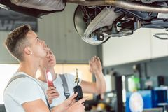Skilled auto mechanic replacing the shock absorbers of a car in workshop. Side view of a skilled auto mechanic replacing the shock absorbers of a lifted car Stock Photos