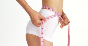 Side view of slender woman measuring waist Stock Image